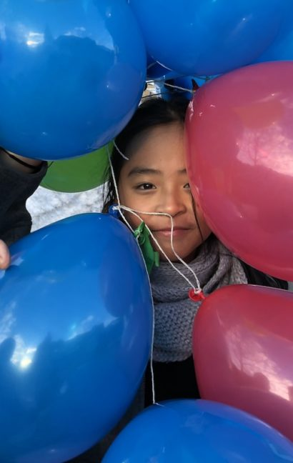 Student behind ballons